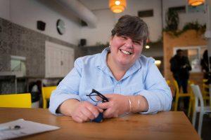 femme souriante avec chemise bleue dans une salle à manger