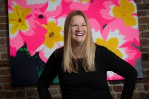 femme souriante devant une toile fleurie et coloré